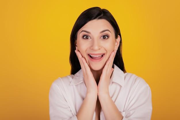 Portrait d'une fille positive étonnée mains joues sur fond jaune