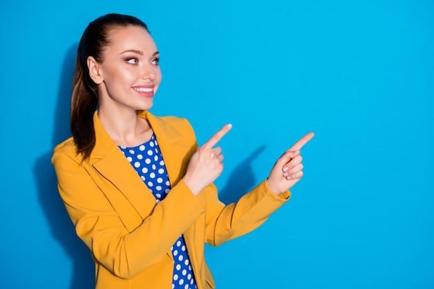 Portrait d'une fille positive et gaie, promoteur de point d'index copyspace démontrer des publicités porter une veste blazer isolée sur fond de couleur bleu