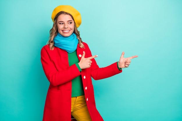 Portrait d'une fille positive et joyeuse, l'index de l'index du promoteur indique que la promotion des annonces recommande suggérer de porter un pull-pantalon isolé sur un fond de couleur turquoise