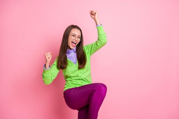 Portrait d'une fille ravie qui gagne à la loterie chanceuse lever les poings crier isolé sur fond de couleur rose