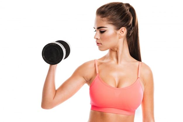 Portrait d'une fille de remise en forme, faire des exercices avec des haltères lourds
