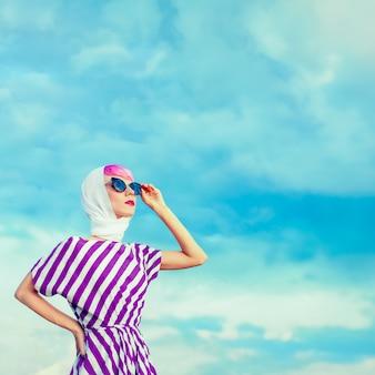 Portrait de fille rétro sur le ciel bleu