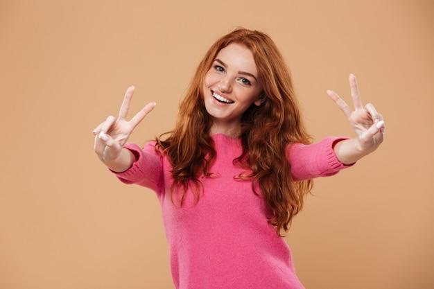 Portrait d'une fille rousse attrayante joyeuse à la recherche avec le geste de la main de la victoire