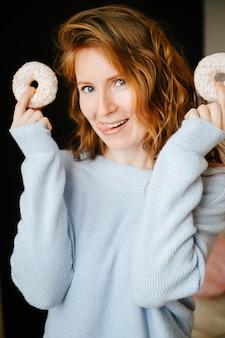 Portrait d'une fille rousse et beignets. cheveux roux qui coule.