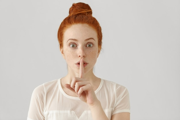 Portrait de fille rousse émotionnelle avec des taches de rousseur et chignon tenant l'index sur ses lèvres