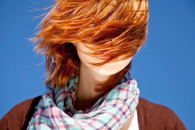 Portrait de fille rousse avec foulard sur fond bleu.