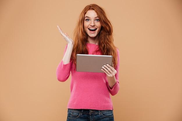 Portrait d'une fille rousse joyeuse heureuse tenant la tablette
