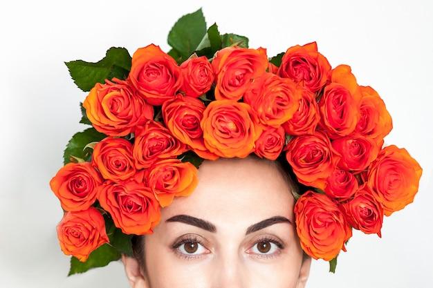 Portrait de la fille rousse qui rit avec des roses orange