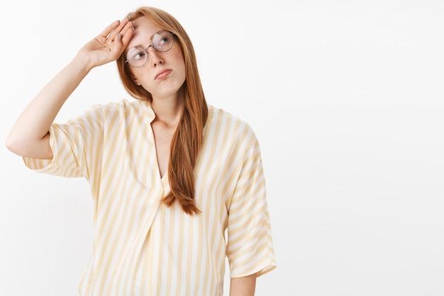 Portrait de fille rousse sombre fatiguée et impassible avec des taches de rousseur dans les verres et chemisier jaune fouettant la sueur sur le front regardant à droite avec un regard épuisé