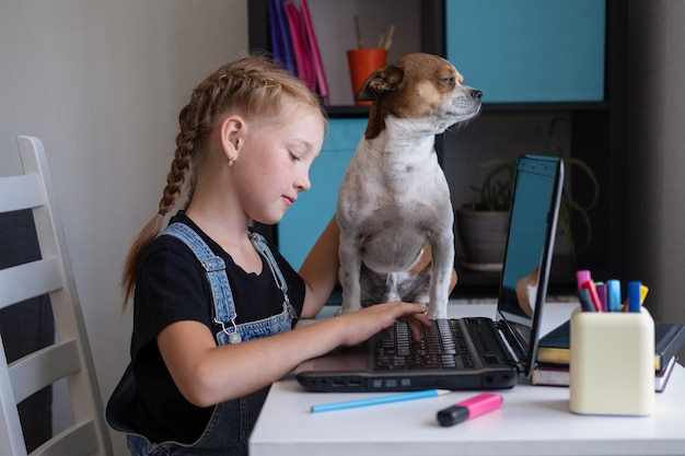 Portrait d'une fille rousse utilisant un ordinateur portable tout en étudiant à la maison avec un chien chihuahua assis sur une table,