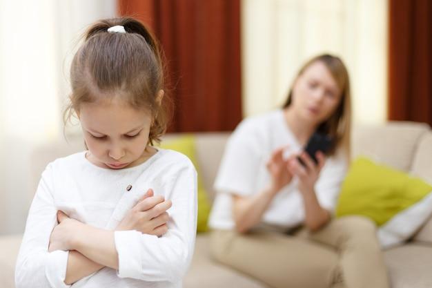 Portrait de fille s'ennuie avec sa mère à l'aide de téléphone portable sur le lit