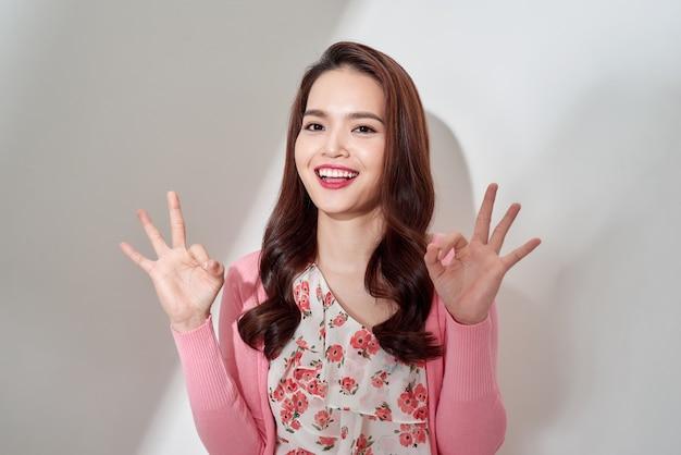 Portrait d'une fille sexy, charmante, jolie, agréable, branchée et riante en robe de fleurs montrant deux signes ok avec les doigts, clignotant avec les yeux à la caméra, isolé sur fond blanc