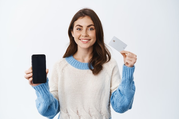 Portrait d'une fille souriante brune avec une émotion joyeuse, montrant une carte de crédit en plastique et un écran vide de smartphone, faisant de la publicité pour une application bancaire mobile, debout contre un mur blanc