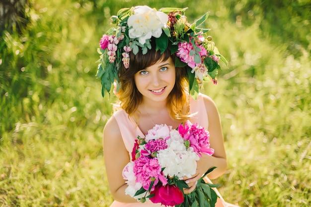 Portrait d'une fille souriante heureuse avec une gerbe de fleurs et un bouquet de pivoines