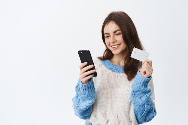 Portrait d'une fille souriante payant dans une boutique internet avec une carte de crédit en plastique et une application mobile, tenant un smartphone et lisant l'écran du téléphone, mur blanc