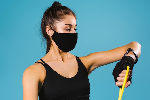 Portrait d'une fille sportive dans un masque de protection se penche sur ses réalisations sur une montre de fitness. bleu