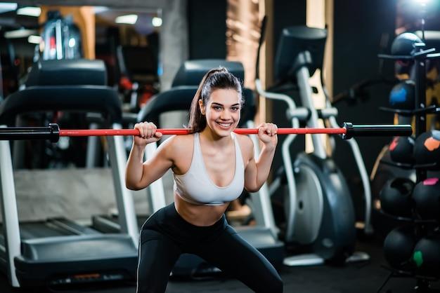 Portrait de fille sportive faisant des squats avec un bar dans le gymnase, souriant à la caméra.