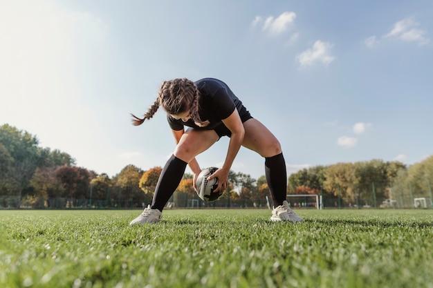 Portrait de fille sportive jouant avec un ballon de rugby