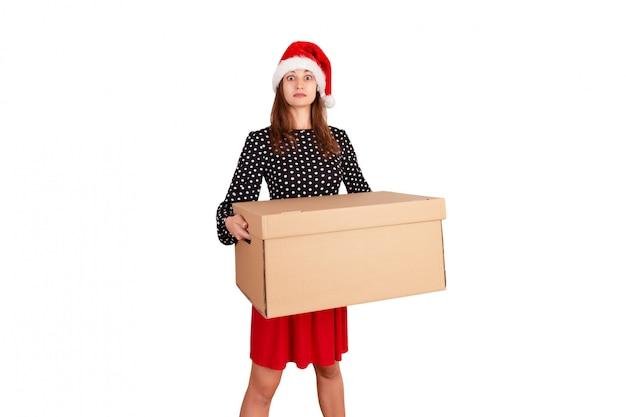 Portrait de fille surprise excitée en robe tenant une boîte-cadeau grosse et lourde. isolé sur blanc vacances