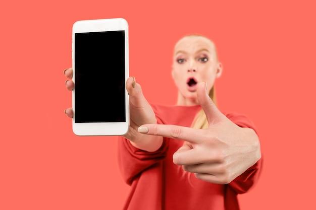 Portrait d'une fille surprise, souriante, heureuse, étonnée montrant un téléphone mobile à écran blanc isolé sur fond de corail.