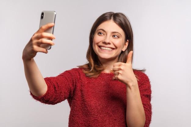 Portrait d'une fille sympathique faisant un appel vidéo via un téléphone portable et montrant les pouces vers le haut, communiquant