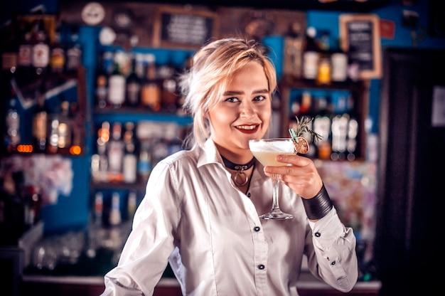 Portrait d'une fille tapster démontrant le processus de fabrication d'un cocktail en se tenant debout près du comptoir du bar en pub