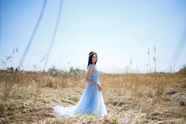 Portrait d'une fille tendre dans une longue robe bleue en pois secs avec un sourire sur son visage par une chaude journée d'été ensoleillée
