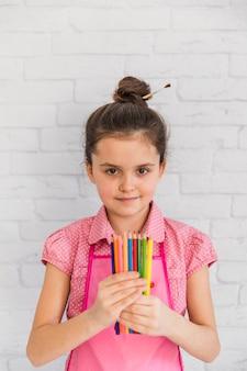 Portrait, fille, tenue, crayons multicolores, main, debout, contre, mur, brique blanche