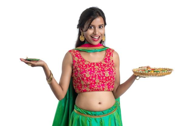 Portrait d'une fille traditionnelle indienne tenant diya célébrant diwali ou deepavali