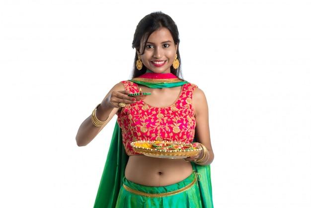 Portrait d'une fille traditionnelle indienne tenant diya, girl celebrating diwali ou deepavali avec holding lampe à huile pendant le festival de la lumière sur fond blanc
