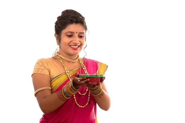 Portrait d'une fille traditionnelle indienne tenant pooja thali avec diya pendant le festival de la lumière sur blanc