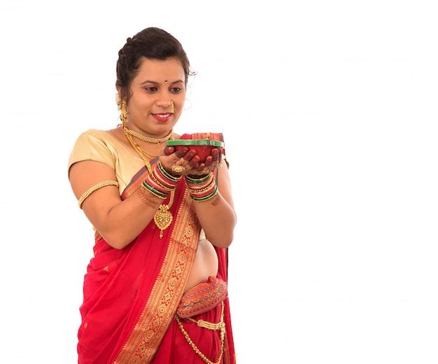 Portrait d'une fille traditionnelle indienne tenant pooja thali avec diya pendant le festival de la lumière sur fond blanc. diwali ou deepavali