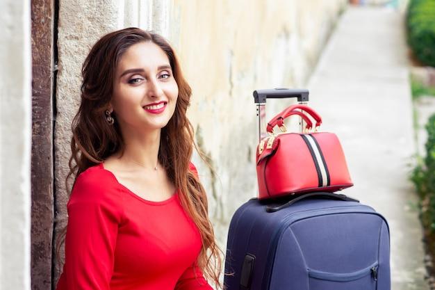 Portrait d'une fille de voyageur assez souriante regarde la caméra avec une valise. notion de voyage.