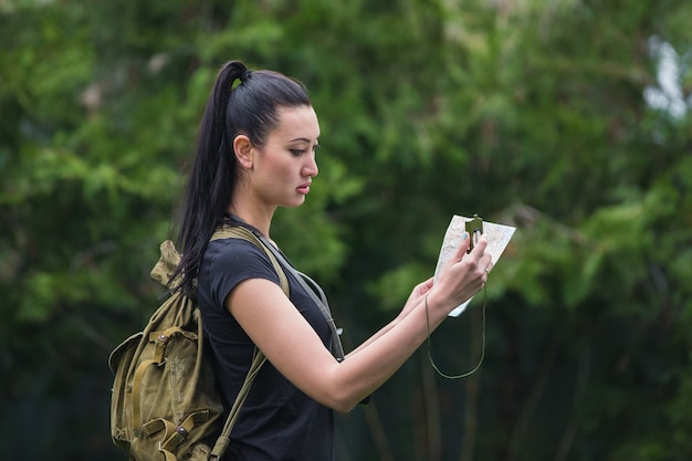 Portrait d'une fille voyageuse dans la forêt avec une boussole