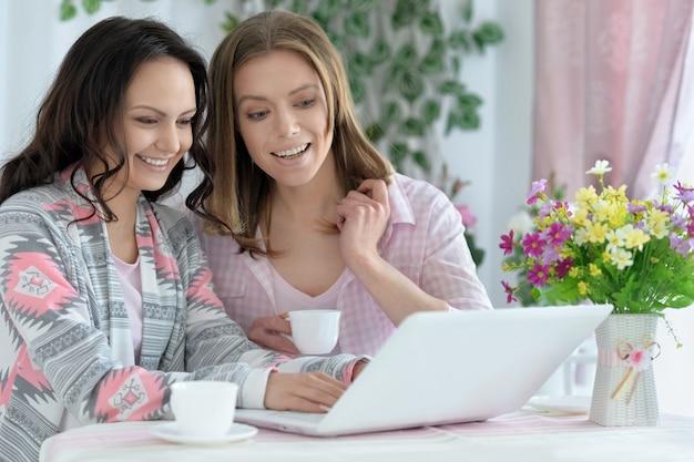 Portrait de filles buvant du café ou du thé avec un ordinateur portable à la maison