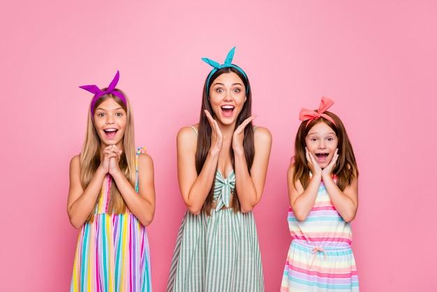 Portrait de filles impressionnées touchant leurs joues criant des nouvelles d'audition portant jupe robe lumineuse isolé sur fond rose