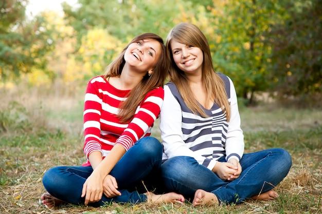 Portrait de filles rousse et brune en plein air.