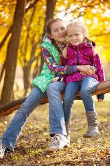 Portrait des filles de soeurs souriantes dans la forêt d'automne