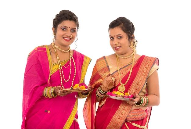 Portrait de filles traditionnelles indiennes tenant diya et fleur thali