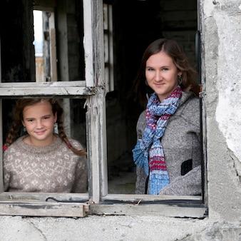 Portrait, filles à travers un cadre de fenêtre altéré