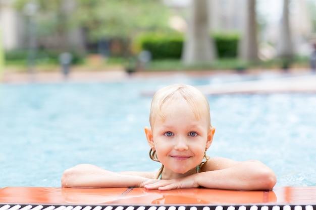 Portrait d'une fillette heureuse dans la piscine
