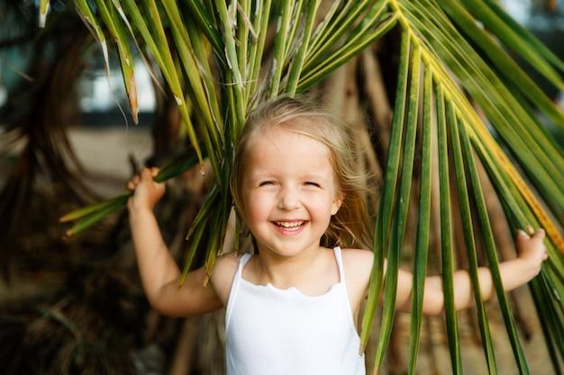 Portrait d'une fillette heureuse avec une feuille de palmier.