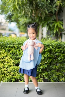 Portrait d'une fillette heureuse en uniforme d'école thaïlandaise avec lapin, prête pour la rentrée scolaire