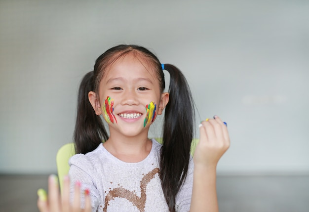 Portrait d'une fillette souriante regardant à travers ses mains colorées et sa joue peinte dans la chambre d'enfant.