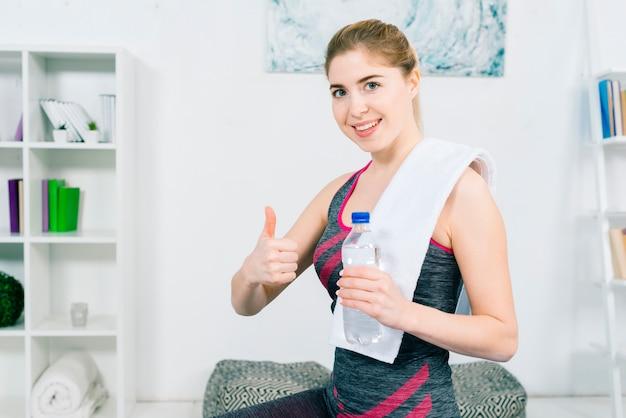 Portrait, de, a, fitness, jeune femme souriante, tenue, bouteille eau, dans main, montrer, pouce haut signe