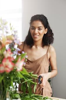 Portrait de fleuriste belle femme africaine souriant faisant bouquet de fleurs.
