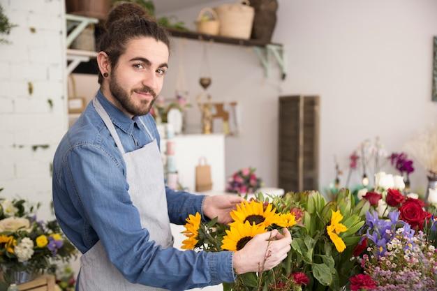 Portrait, de, a, fleuriste mâle, arranger, bouquet fleurs, regarder, à, appareil photo