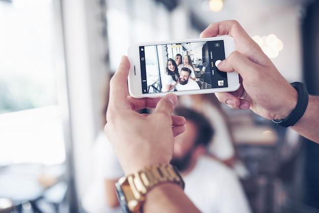 Portrait de flou de bonheur jeunes meilleurs amis avec les mains tenant le téléphone au premier plan