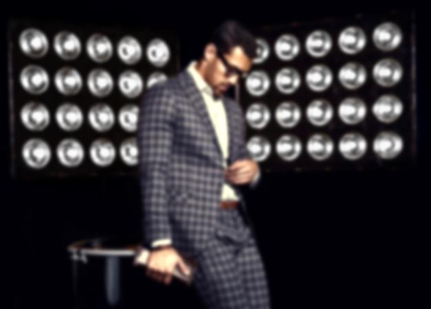 Portrait flou de mannequin homme sexy beau mode homme habillé en costume élégant sur fond de lumières de studio noir