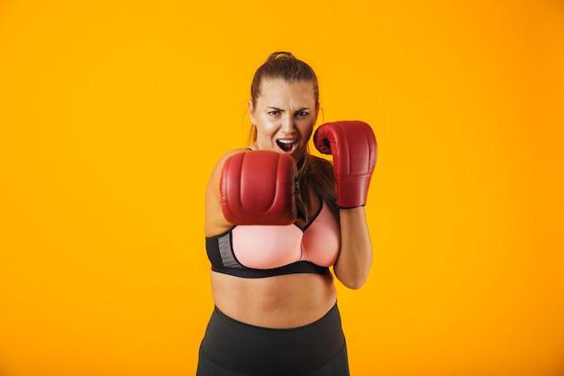 Portrait de forte grande sportive en soutien-gorge sportive portant des gants de boxe pratiquant, isolé sur fond jaune
